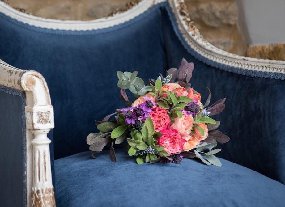 blue velvet chair and flower girls posy