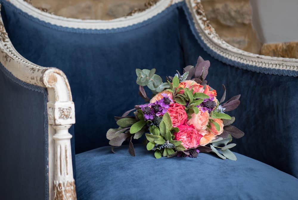 blue velvet chair and flower girls posy