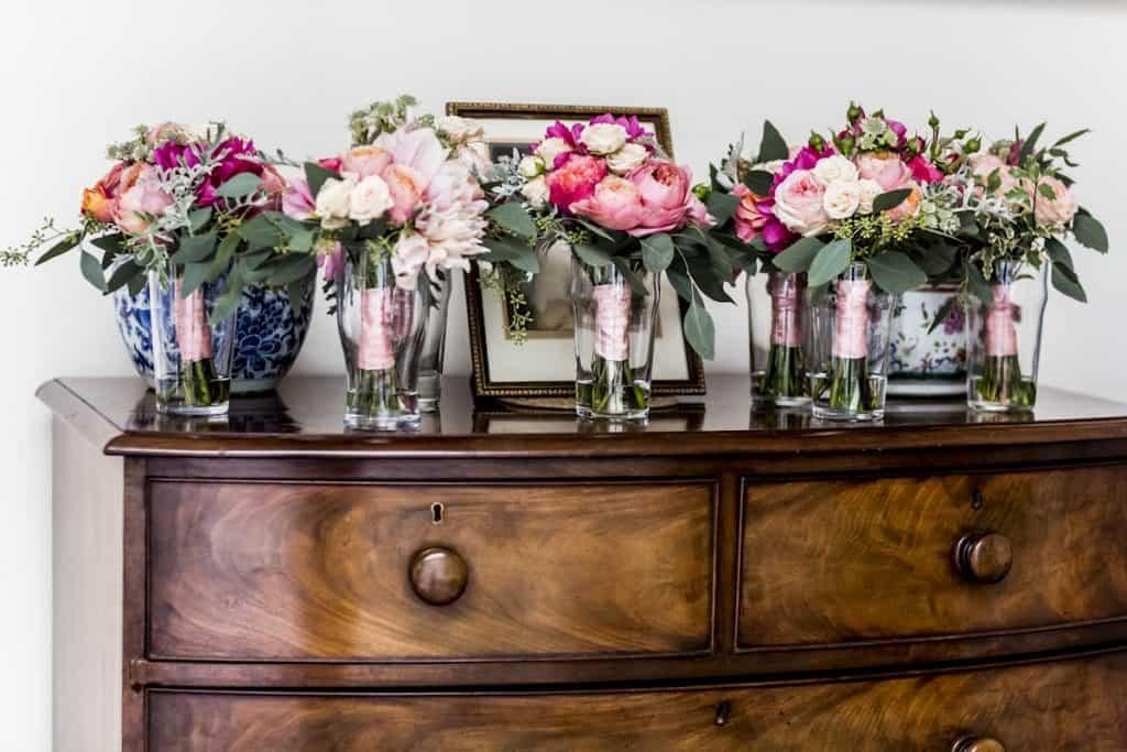 Blush coloured arrangements in bottles
