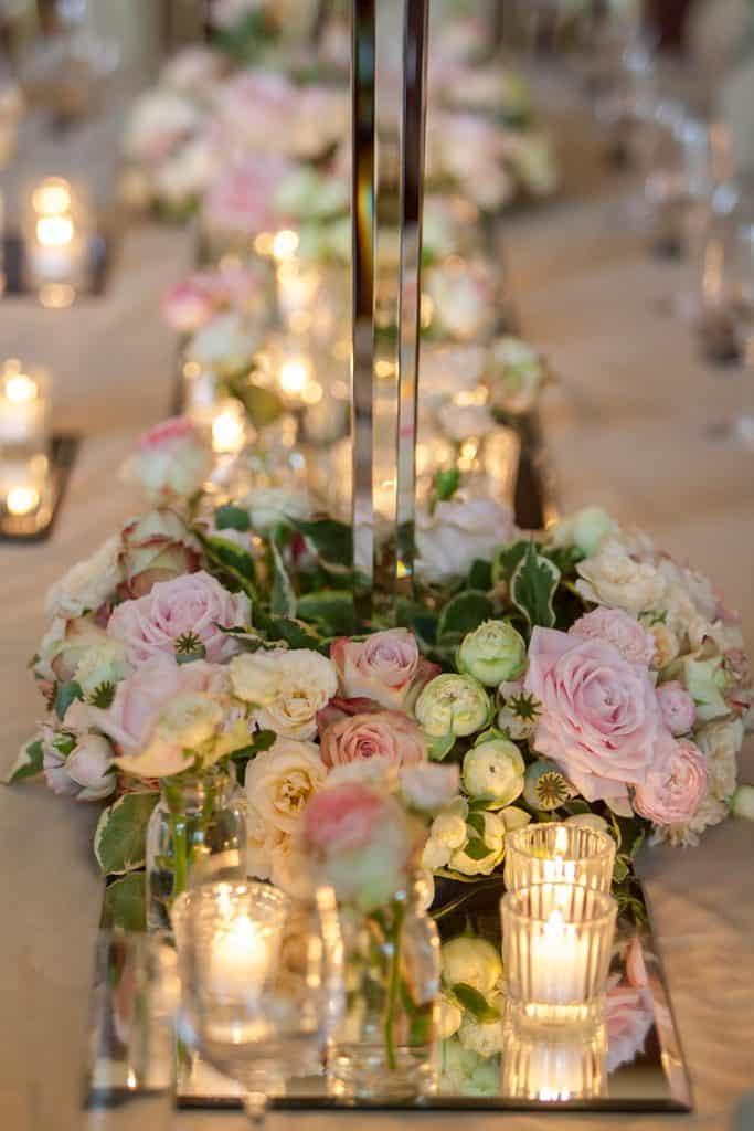 Pink roses at base of candelabra