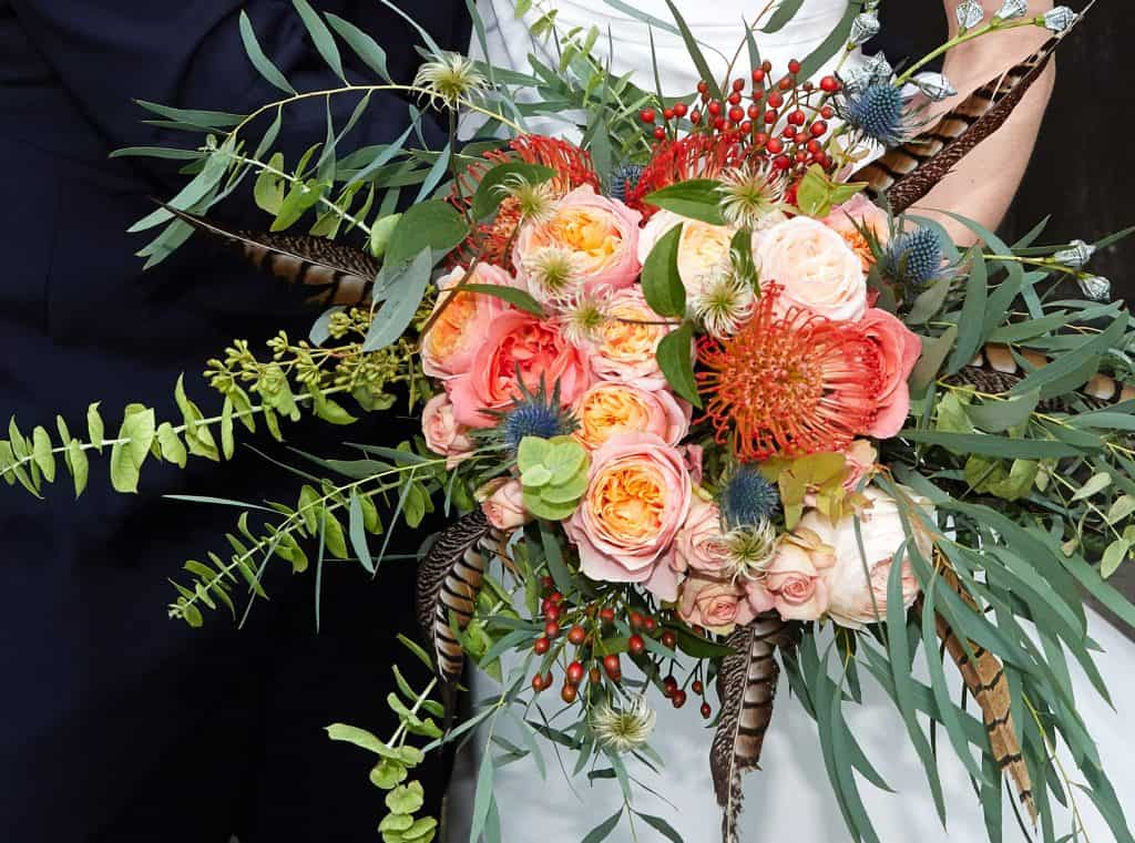 bridal bouquet with roses and feathers